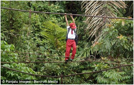 Children use high wires to cross the river, 30 feet below, to get to school in Padang, Indonesia