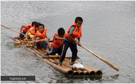Elementary school students row a raft to school in Gulong township, Southwest China