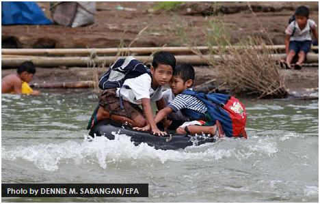 Students use an inflated tube to cross this swollen river on their way to school in a remote village in the Philippines' Rizal province