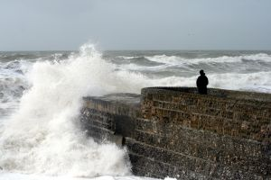a person sitting on a break water in a stormy sea