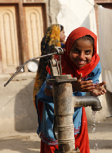 Children in Sindh, Pakistan, play at a water pump in a village